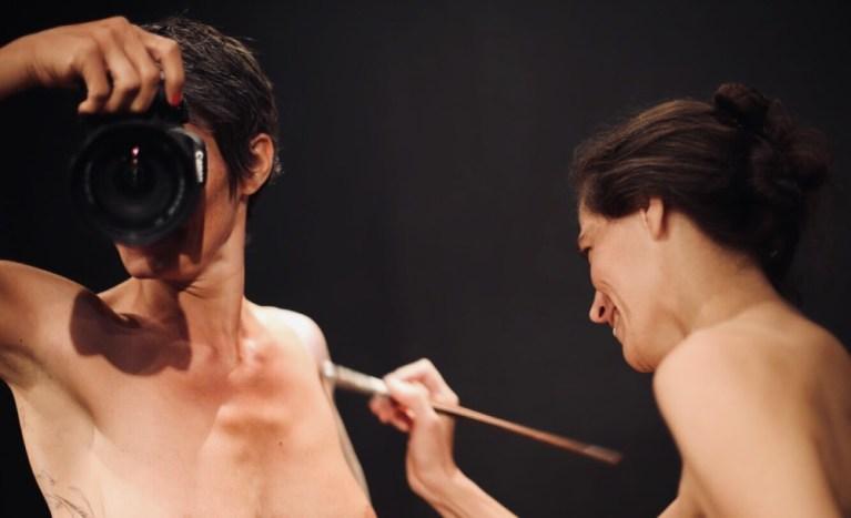 portrait femme derrière un appareil photo nue se faisant peindre par une autre femme