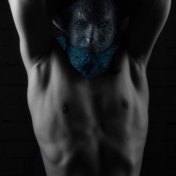 Homme nu la tête dans un tissu bleu les mains derrière la tête