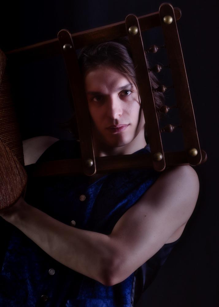 Homme en séance photo portrait en clair obscur portant une chaise à barreaux