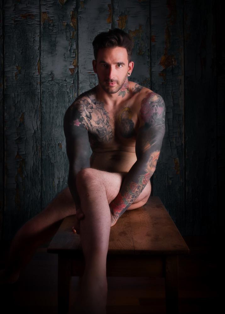 Homme tatoué et handicapé en nu artistique assis sur une table basse en clair obscur