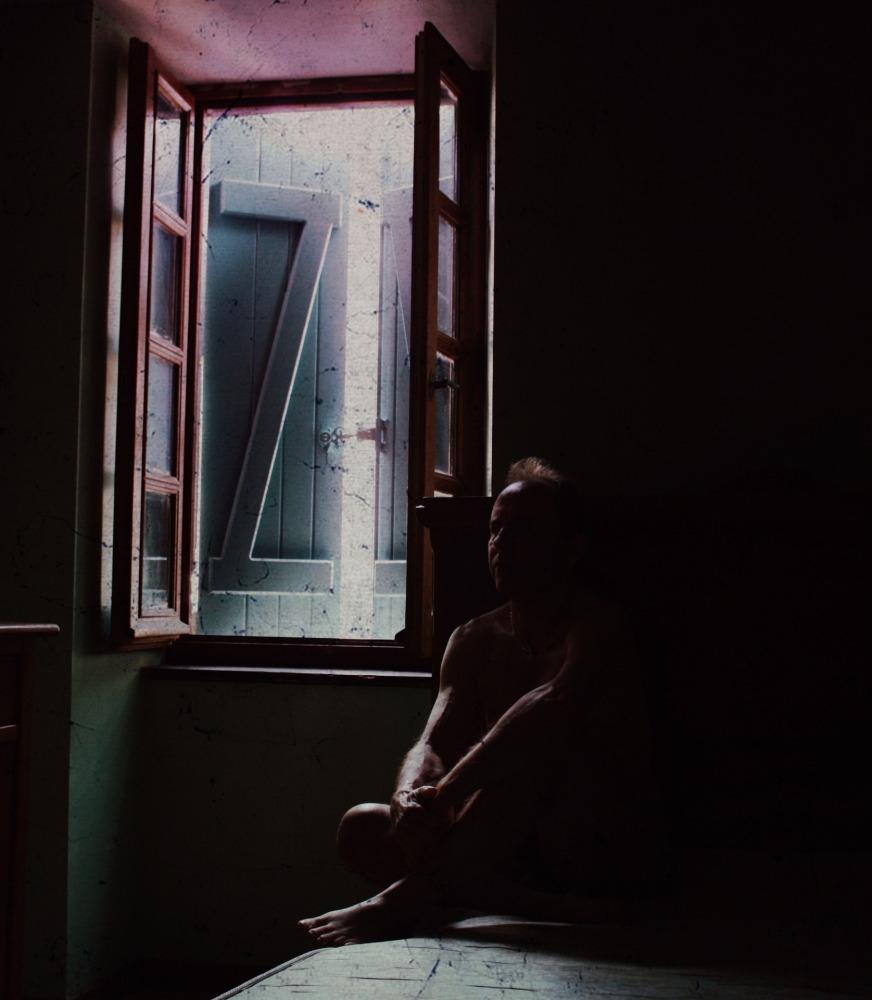 Homme en nu artistique dans l'ombre d'une fenêtre aux volets fermés