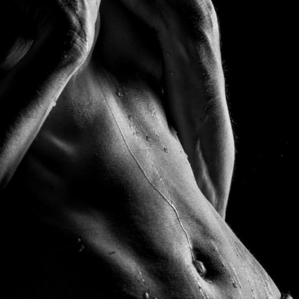 ventre de femme en ne artistique les mains sur les seins en clair obscur