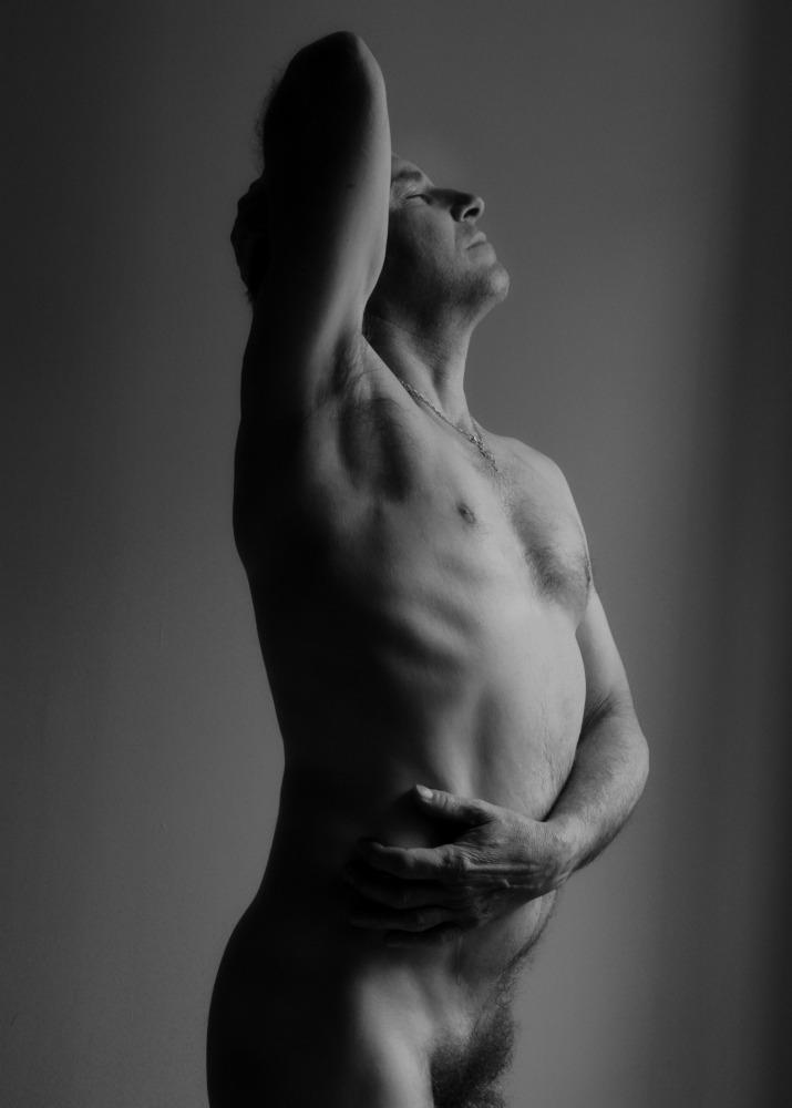 Homme mature en nu artistique et clair obscur noir et blanc de profil debout