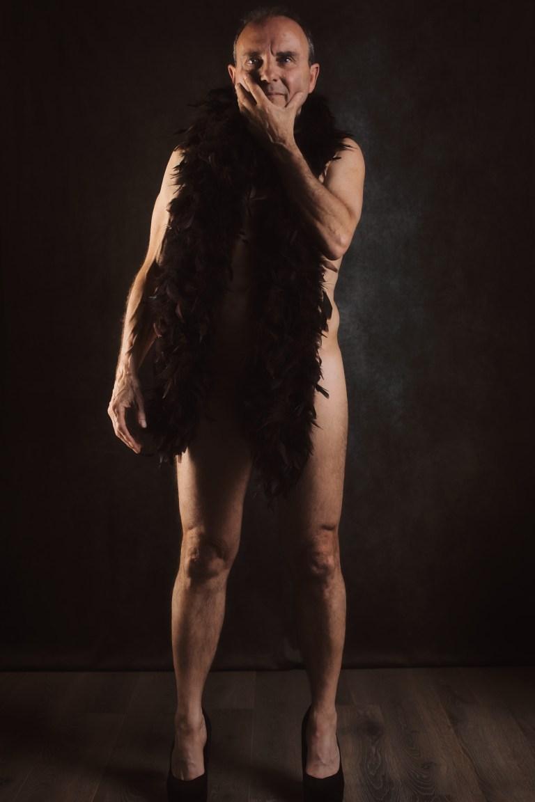 homme mature en nu artistique portant des talons hauts et un boa noir