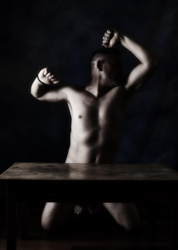 Homme en nu artistique clair obscur à genou derrière une table les bras en l'air