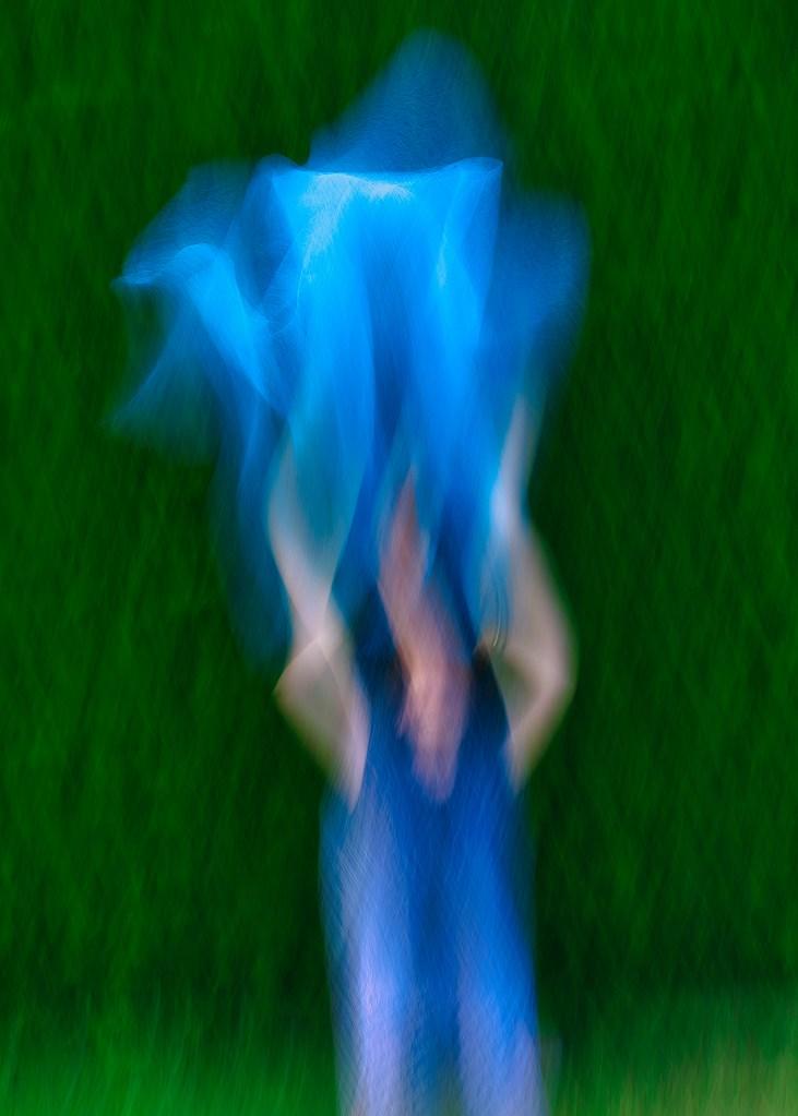 Personnage jouant avec un tissu bleu en flou artistique icm