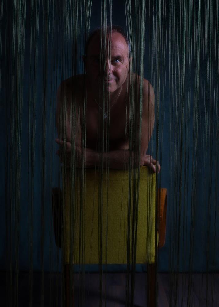 portrait homme en nu artistique sur un fauteuil vert derrière un rideau à franges