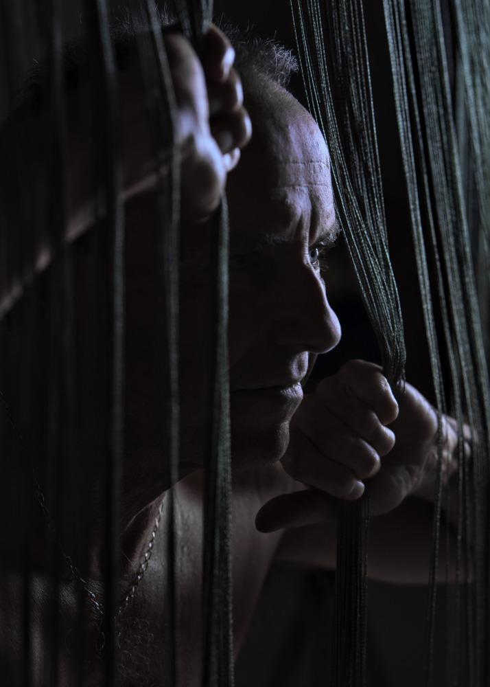portrait d'un homme mature en clair obscur derrière un rideau à franges