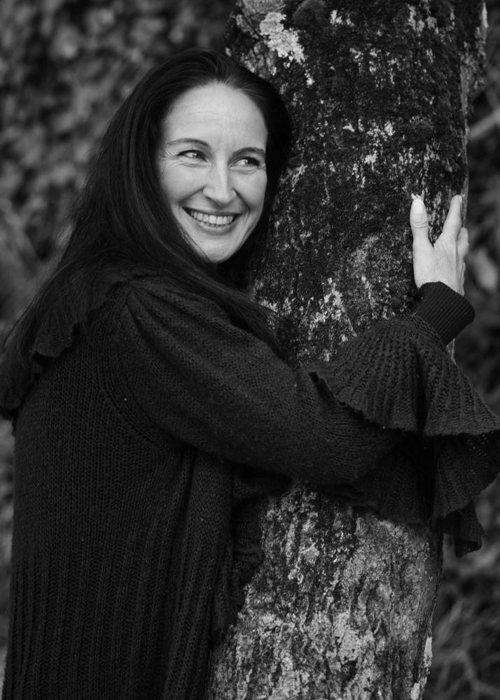 portrait en noir et blanc d'une femme aux cheveux longs calinant un arbre