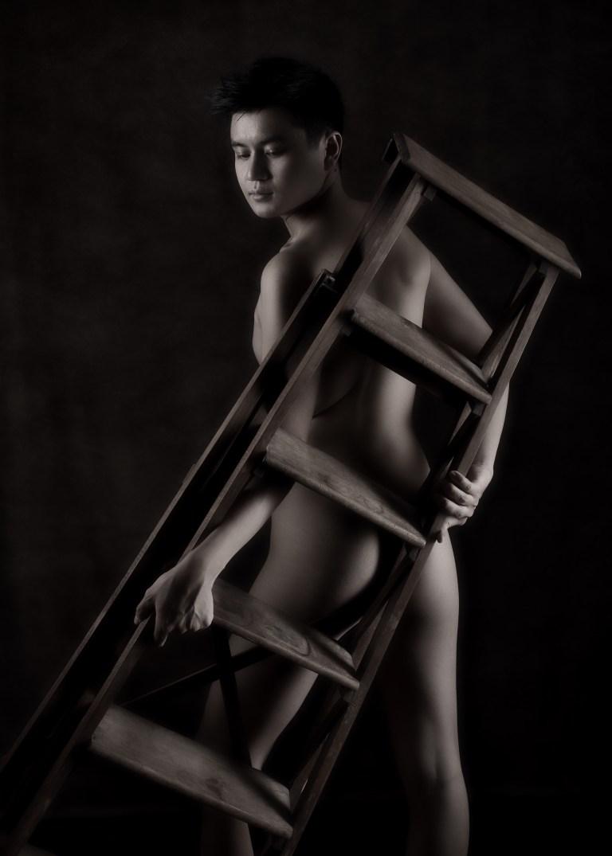 homme asiatique modèle en nu artistique clair obscur derrière un vieil escabeau en bois