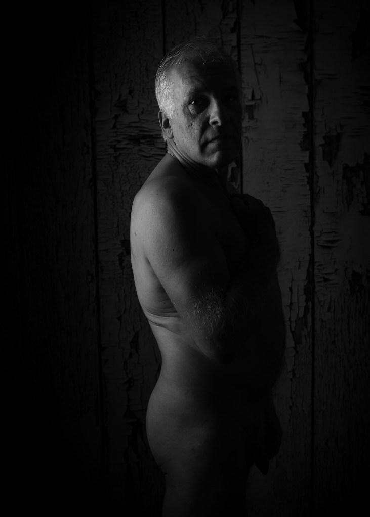 homme en nu artistique en clair obscur debout de profil en noir et blanc