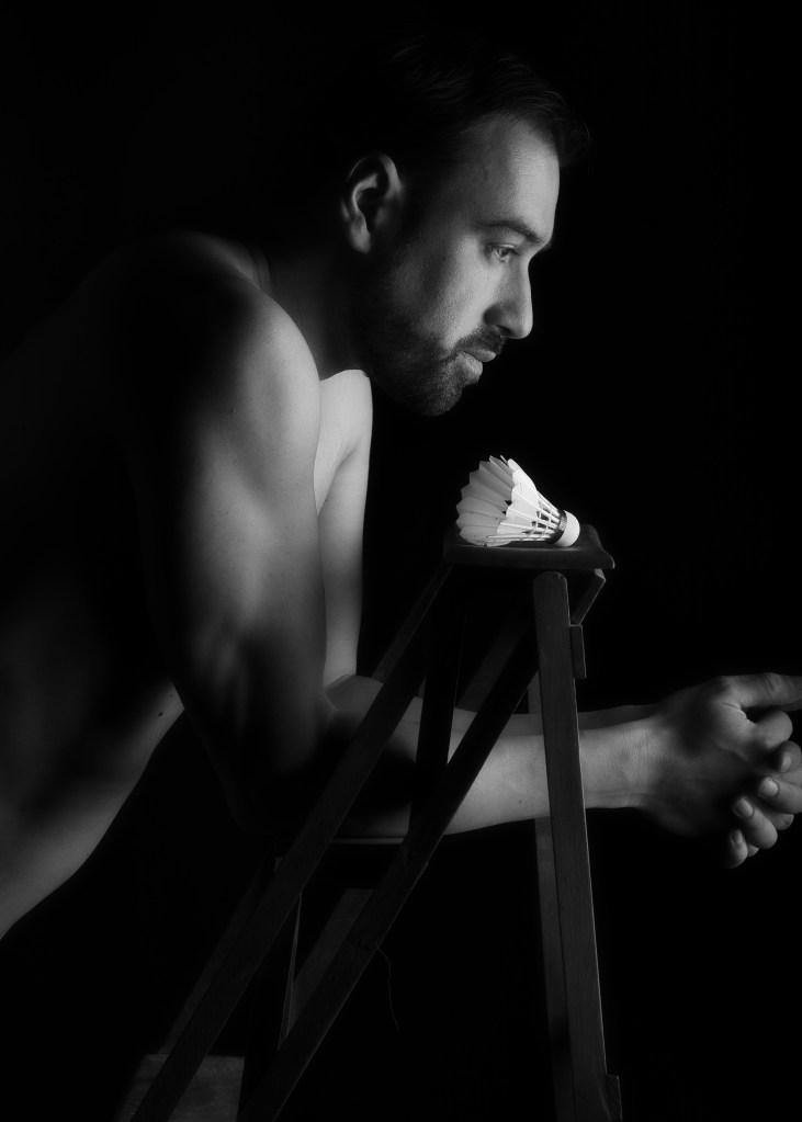 portrait noir et blanc de profil d'un homme en clair obscur avec un volant de badminton