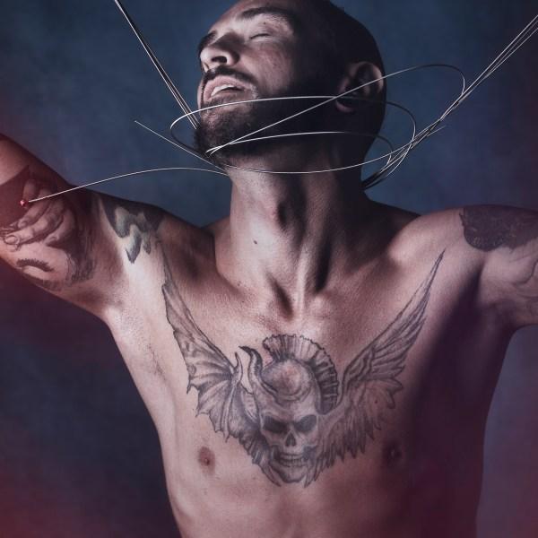 nu artistique homme tatoué jouant avec des cordes de basse