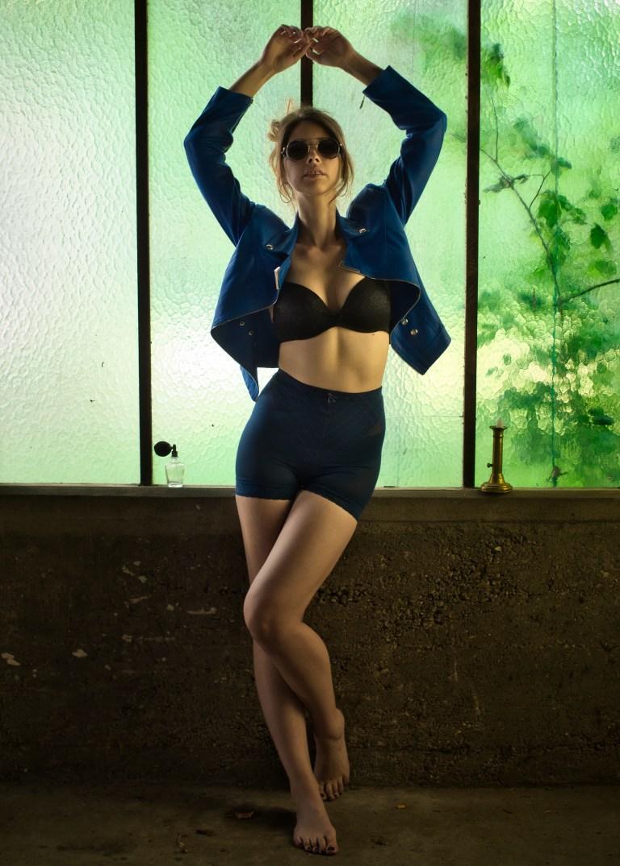 femme en lingerie vintage dans un entrepôt d'artiste devant une vitre verte