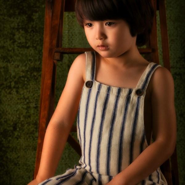 portrait enfant eurasien en clair obscur en salopette sur un escabeau en bois