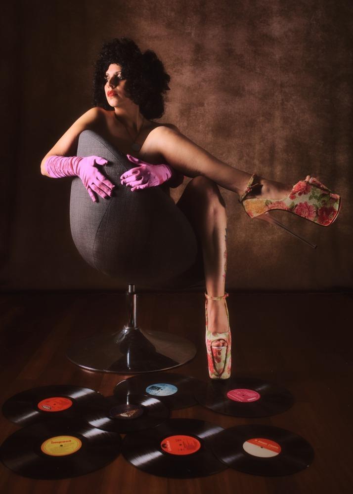 femme en nu artistique dans un style rétro disco portant des gants roses et des chaussures compensées à fleurs roses sur une chaise boule devant des vinyles au sol