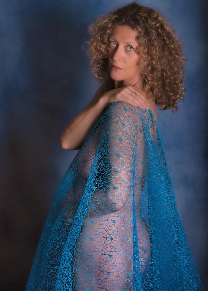femme en nu artistique aux cheveux dorés bouclés yeux bleus sous un tissu bleu