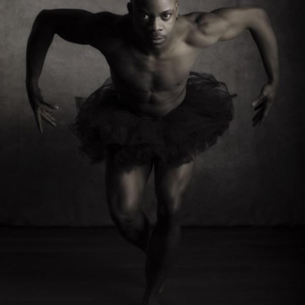 modèle homme black en nu artistique portant un tutu noir en position de danse en clair obscur